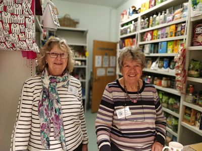 Two female volunteers smile through the shop serving hatch