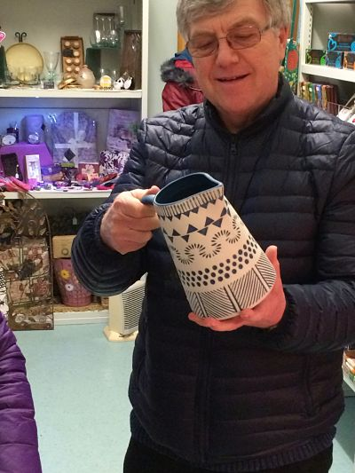 Shop volunteer admires a large pottery jug engraved in blue on cream with cream interior
