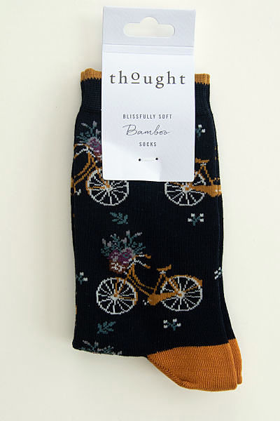 Bicycles with baskets at the front containing flowers on a black sock with mustard colour heels and toes and a mustard colour line around the top of the cuff