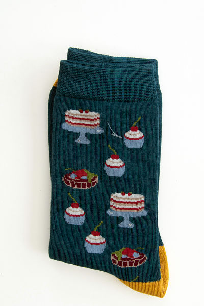 Large cakes on stands and small cupcakes in shades of blue, red and white with cherries on top on a dark green sock with mustard toes and heels.