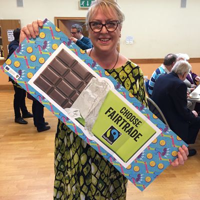 Female customer holds up Choose Fairtrade poster in the hall at St Andrew's Church