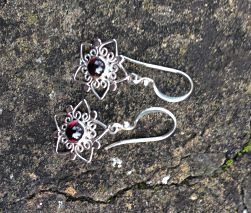 Hook earrings with sterling silver wire worked into a five petal flower shape with central garnet gem.
