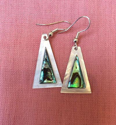 A triangle of abalone shell is mounted on a larger triangle of mother of pearl which creates a glossy white frame for the blue and green of the abalone. Suspended from silver plated hooks at the apex of the triangle.