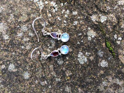 Hook earrings. Silver encloses a teardrop garnet with a silver enclosed round moonstone below.