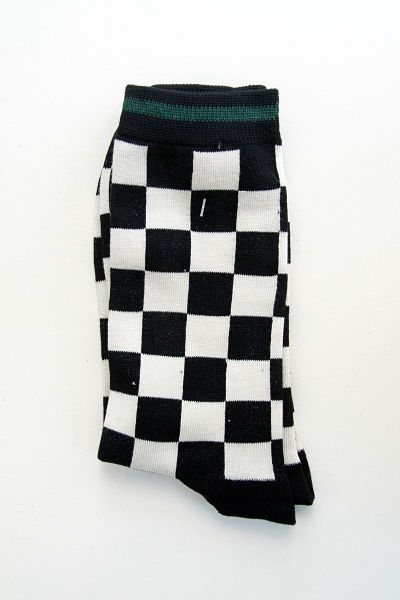 The socks have a chequer design in black and white with black heels and toes. The cuff is black with a thin green stripe around the centre.