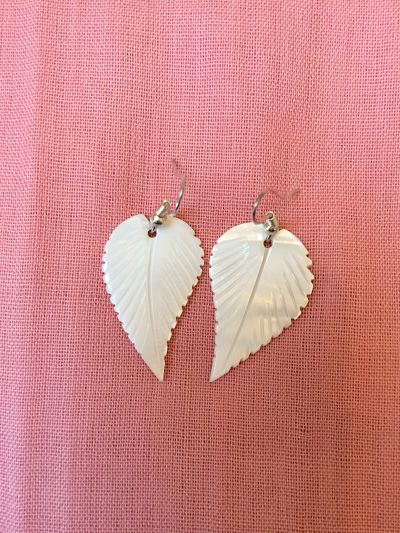 Hook Earrings. Glossy white mother of pearl leaves suspended from silver plated hooks. The leaves are lightly engraved to show the vein structure