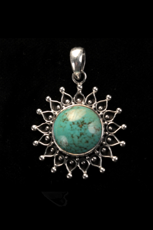 Stunning round dome of turquoise mounted on flat sterling silver and clasped in a surround of open work decorative silver.
