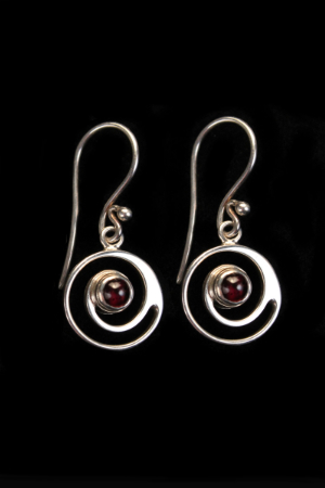 A double swirl of silver with a garnet gem in the centre.