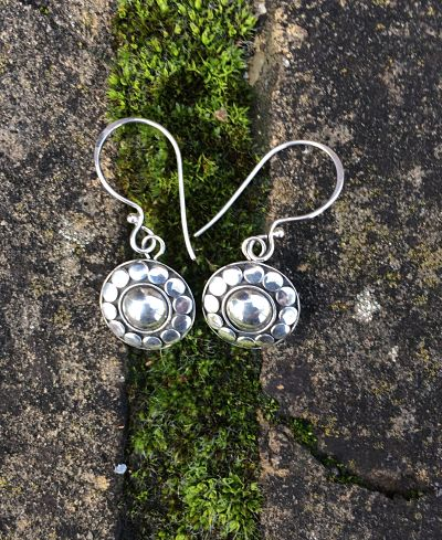 Hook earrings. 12 small flat circles of silver form a rim around a slightly domed silver centre.