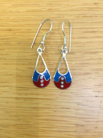 The enamelled decoration on these earrings gives the effect of a blue turn down collar on a red cardigan with three silver coloured buttons down the front.