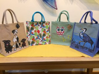 Bag 1: Design of Great Dane with a smaller dog friend of each side of the Great Dane. Design in black, brown and white on natural coloured jute. Bag 2: Brightly coloured birds fly against a background of tropical leaves and flowers on a cream background with turquoise handles. Bag 3: A red owl with large white spots and huge blue rimmed eyes sits on a branch against a background of soft green which is repeated in the handles and edging of the bag. Bag 4: Design in shades of blue, grey and white with blue handles and bag edging, a heron walks along the edge of a body of water.