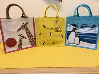 First design: depicts heads and necks of an adult and young giraffe with reddish/brown tropical sun on natural coloured jute, bag edging and handle match the sun. Second bag: yellow including handles with a design of bees on the cells in a honeycomb with the wording 'Save Our Bees'. Third Bag: Design on a background of turquoise of adult penguin and chick standing snuggled together against a scene of snow, ice and water.