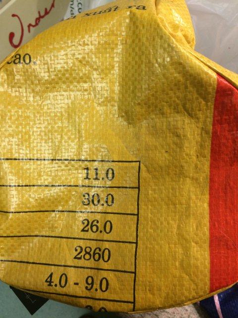 Made from yellow cement bag, the cover has numbers printed in black and an wide orange stripe on one side